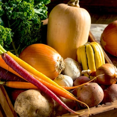 photo if a crate with onions, potatoes, squash, and carrots