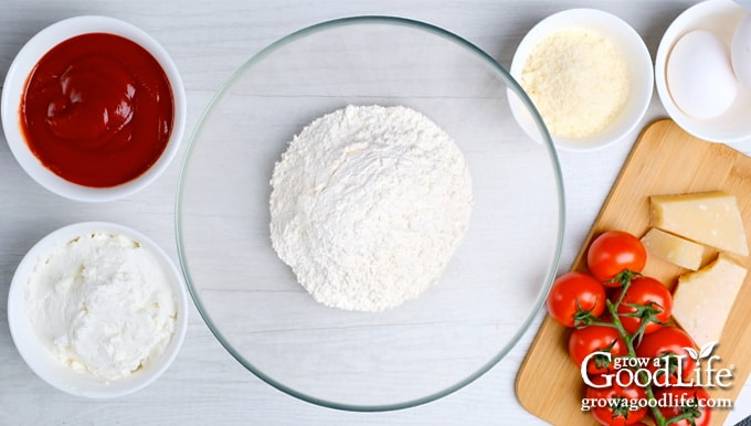 Bowl of flour surrounded by bowls of ingredients in recipe