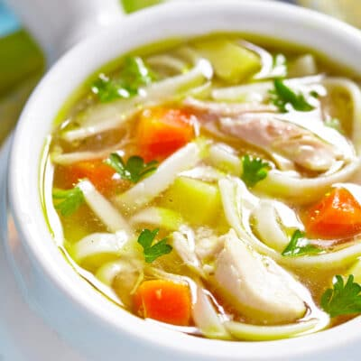 closeup photo of turkey noodle soup in a white bowl