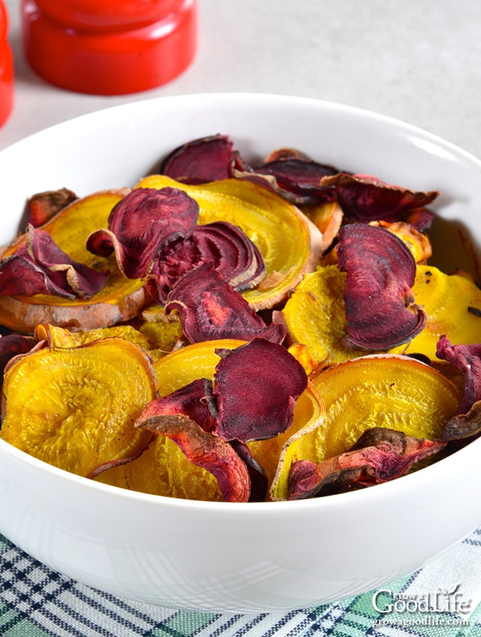 gold and red beet chips in a white bowl
