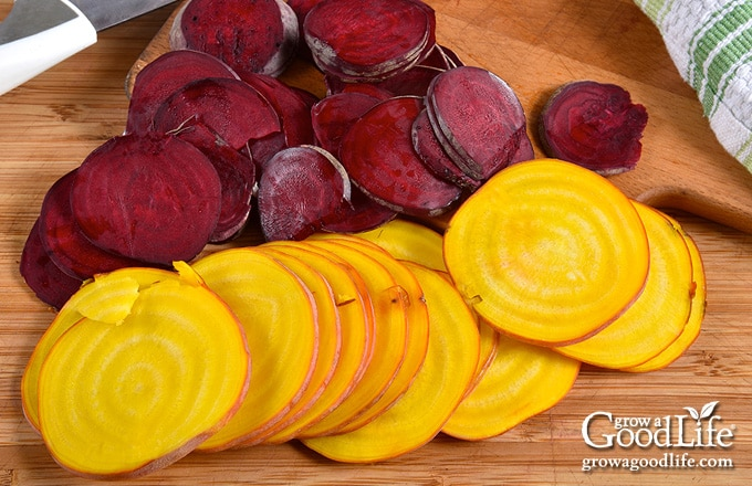 sliced gold and red beets on a cutting board