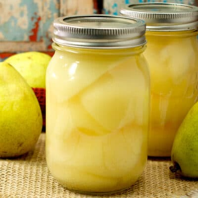 fresh pears and jars of canned pears on a table