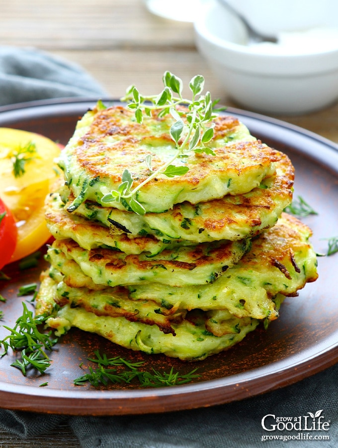 a stack of zucchini fritters on a brown plate