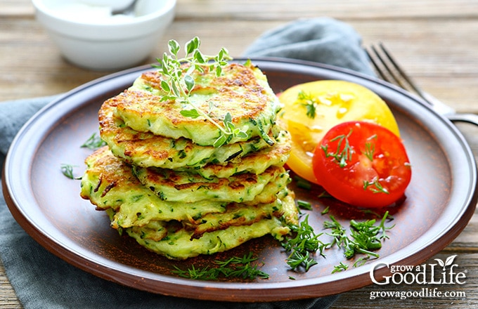 stack of zucchini pancakes and sliced tomatoes on a brown plate