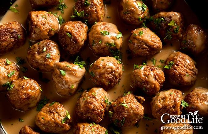 overhead image of meatballs simmering in cream sauce