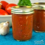 jars of home canned pizza sauce on a blue towel