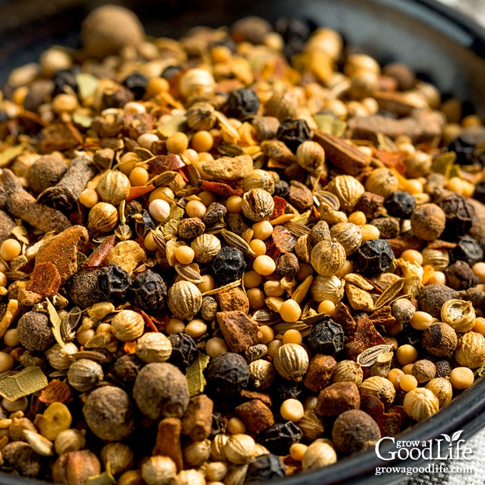 close up photo of homemade pickling spice mix in a black bowl