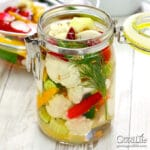 jar of mixed vegetables and pickling brine on a table