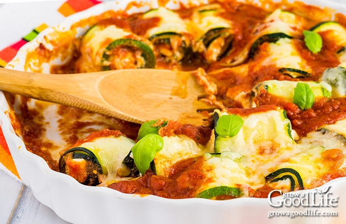 close up of baked cheesy zucchini roll ups casserole on a table