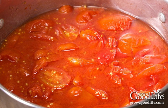 overhead image of a pot of cooked tomatoes on the stove