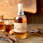 bottle of homemade vanilla extract on a table with vanilla beans
